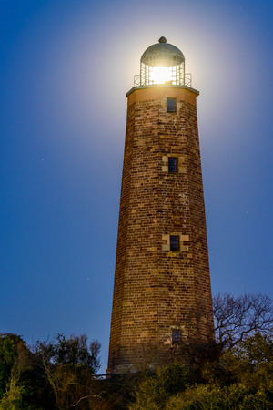 Image of the old Cape Henry Lighthouse located at the mouth of the Chesapeake Bay situated on Fort Story in beautiful Virginia Beach, Virginia  A full moon is shining through the lighthouse Фото со стока