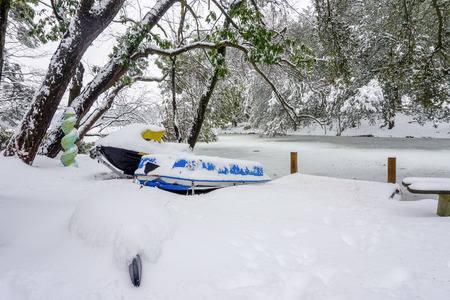 peddle: a snow covered kayak, jet-ski, and peddle boat sitting next to a frozen lake