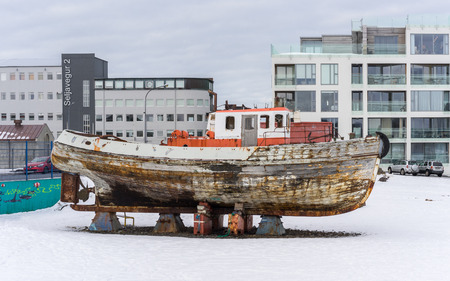 Reykjavik: An old wooden boat on blocks awaiting repair in the waterfront district of Reykjavik Iceland.