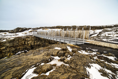 diverging: The Bridge between two continents at Sandv�k, on the  Reykjanes peninsula of south west Iceland, is a small footbridge over a major fissure which provides clear evidence of the presence of diverging North American and Euro-Asia tectonic plates Stock Photo