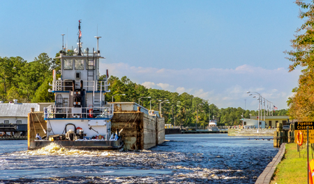 An HDR image of a barge tugboat pushing a couple of barges towards the opening of the Great Bridge Locks in Chesapeake Virginia heading North to Norfolk. Stock Photo