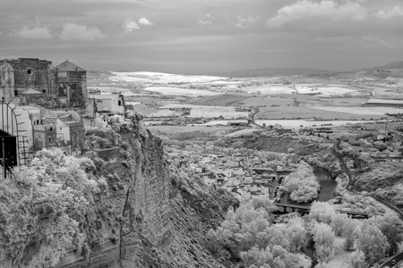 Infrared view of the hillside looking down of the white hilltop town of Arcos de la Frontera, Cadiz Spain