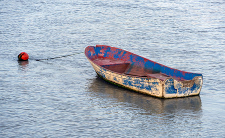 A small fishing skiff tied to a mooring bouy in Spain Stock Photo