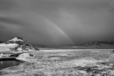 An infrared photo of the south of Iceland showing mountains, grass, and a rainbow.
