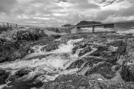 A stream that cascades under a bridge in the west of Iceland Stock Photo