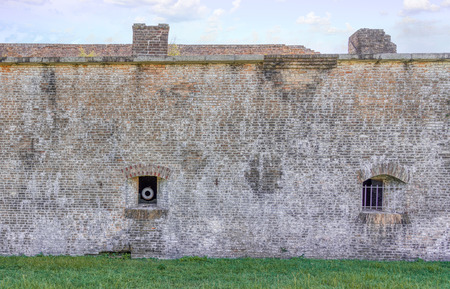 A Civil War canon peers out of the fortifications of Fort Pickens, Fl.
