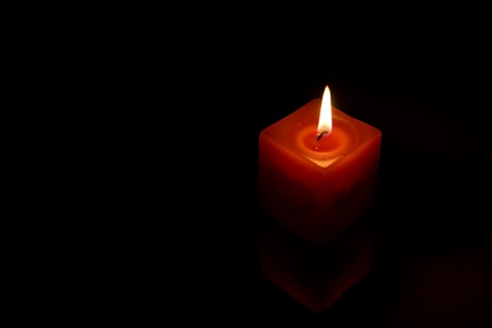 Red candle in dark room Stock Photo