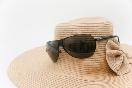 Sunglasses and a hat for summer season on white background photo