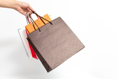 carry on bags: Holding shoping bags by hand on white isolate