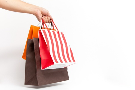 Holding shoping bags by hand on white isolate