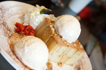 Ice-cream with bread and strawberry on white dish photo