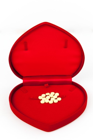 Medicines in heart shape luxury box on white isolate photo