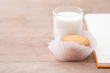 Milk with cookie and notebook on wood table photo