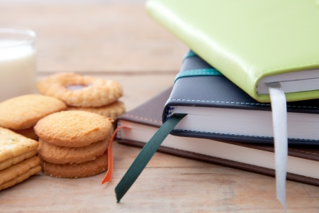 Notebook stack and some dessert on table Stock Photo - 14512688