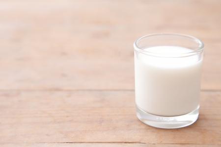 melk glas: Melk op houten tafel achtergrond Stockfoto