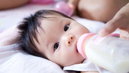 Pretty baby girl is drinking milk Stock Photo