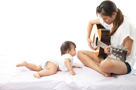 Mother is playing a guitar for her baby