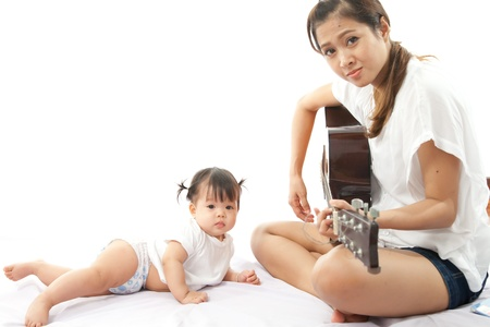 Mother is playing a guitar for her baby photo