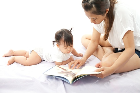 Mother is reading a book for her baby photo