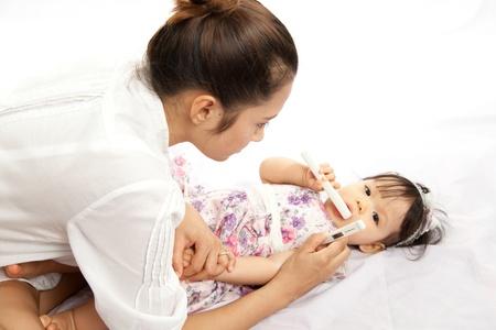 엄마는 아기의 온도를 측정한다 스톡 콘텐츠