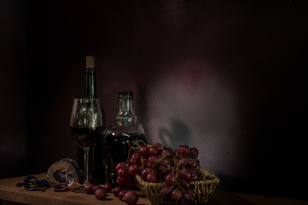 Still Life ,Vine of grape with wine on wooden table.