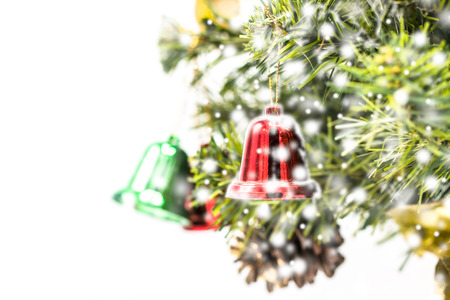 red and green and gold christmas bell decoration hanging from christmas treechristmas tree background