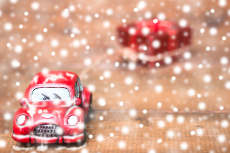 Red beetle car are dragging red gift box on snowing on old and rustic wooden background. using for Christmas greeting card, New Year and happy birthday present decoration concept.