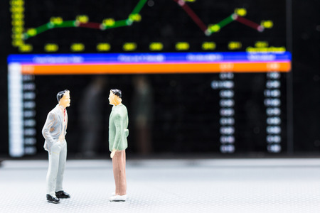 Miniature people : small figures businessmen stand and look at Stock Exchange Board Background with copy space and using as background finance business team competition concept, business plan concept.