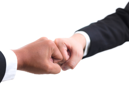 Close up of young asian businessman making a fist bump on white background. Business people wear suit do a fist pump together after good deal. Business success and teamwork concept.