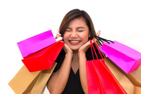 Beautiful young Asian woman with colorful carry shopping bags in her hands smile and happiness. over a white background.