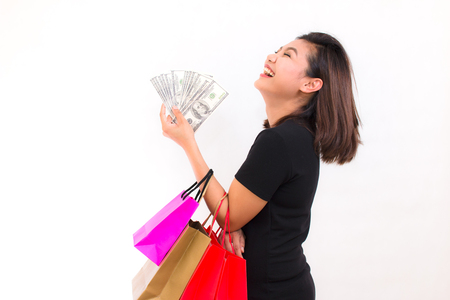 Beautiful young Asian woman with colorful shopping bags. One hand holds money one hundred dollar bill on white background.