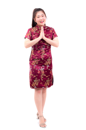 Asian woman wearing chinese dress cheongsam with gesture of congratulation, bring the hands together in greeting or obeisance and smile in Chinese New Year Festivities, New Year Celebration isolated. Banque d'images