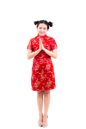 Asian woman wearing chinese dress cheongsam with gesture of congratulation, bring the hands together in greeting or obeisance and smile in Chinese New Year Festivities, New Year Celebration isolated. Stock Photo