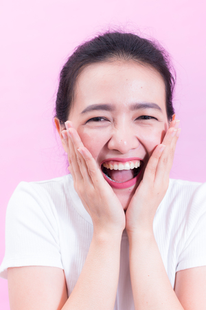Portrait of beautiful Young Asian woman black hair wear a white t-shirt. with shocked facial expression. Portrait of surprised beautiful girl holding her head in amazement and open-mouthed.