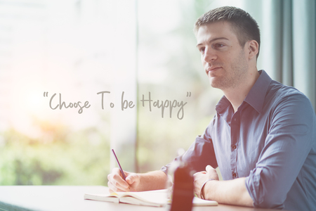 Positive thinking concept. Portrait of a handsome businessman looking to the left and sitting on desk and writing on notebook with message choose to be happy on space in the picture.