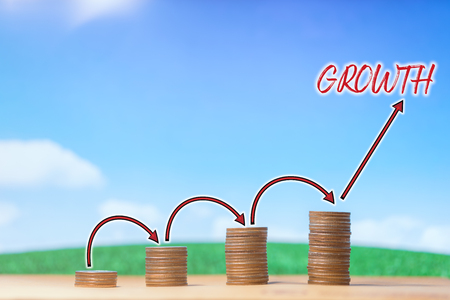 Investment, financial, business concept. Money of coin stack with arrow step up growing growth on blue sky and white cloud. Several piles of coins as symbol of invest. With copy space.