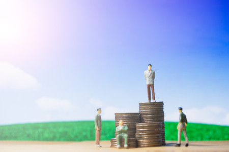 Miniature people small figures businessman stand on money of coin stack step up growing growth on blue sky and white cloud. Business, Successful, investment, financial concept, with copy space.