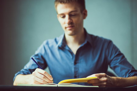 Close up of the hands of a businessman in a blue shirt signing or writing a document on a sheet of notebook. businessman or student writes information from portable prepare for lectures, Vintage color