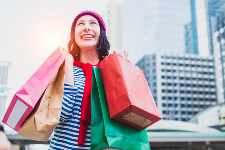 Portrait of an excited beautiful young girl wear shirt and wool hat holding many shopping bags and smile. With copy space. Woman shopper smiling happy. Beautiful young Caucasian. lifestyle, discount