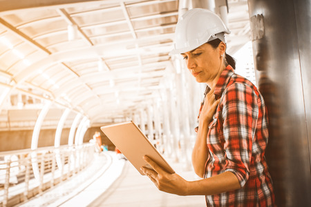 Industrial construction engineer wear safety helmet engineering working and using digital tablet on building outside. Engineering tools and construction concept. Business industry concept. copy space. Stock Photo