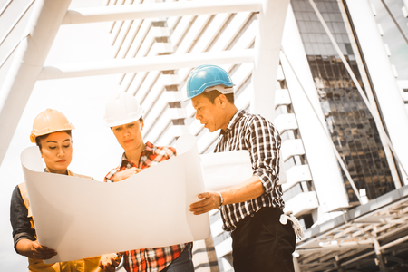 Three Industrial engineer wear safety helmet engineering working and talking with drawings inspection on building outside. Engineering tools and construction concept. With copy space