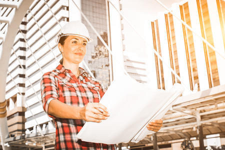 Industrial construction engineer wear safety helmet engineering working inspection and smile on building outside office. Engineering tools and construction concept. With copy space for your text.