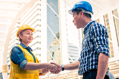Construction and engineer concept. Construction worker in protective uniform shaking hands meeting for architectural project working with partner. Worker and customer having agreement in factory. Stock Photo