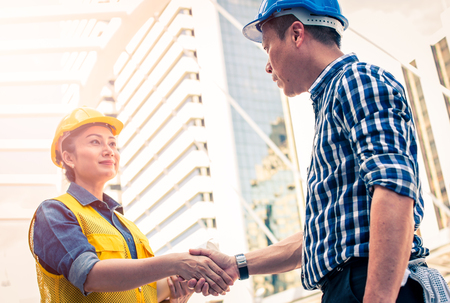 Construction and engineer concept. Construction worker in protective uniform shaking hands meeting for architectural project working with partner. Worker and customer having agreement in factory.