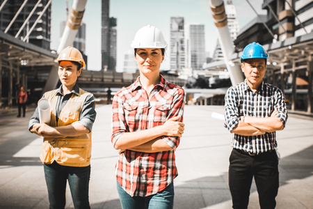 Three Industrial engineer wear safety helmet engineering standing with arms crossed holding inspection tablet and smile on building outside office. Engineering tools and construction concept.