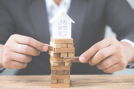 Businessman hand holding wood block with model white house. Investment risk and uncertainty in the real estate housing market. Property investment and house mortgage financial concept. with copy space Foto de archivo