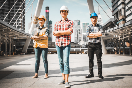 Three Industrial engineer wear safety helmet engineering standing with arms crossed holding inspection tablet and smile on building outside office. Engineering tools and construction concept. Stock Photo