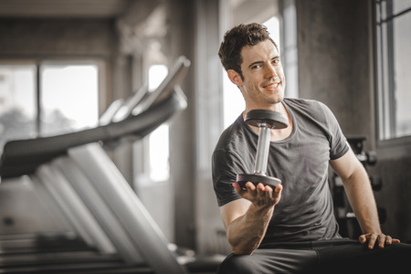 Fit caucasian handsome young man and big muscle in sportswear. Young man holding dumbbell during an exercise class in a gym. Healthy sports lifestyle, Fitness concept. with copy space for your text.