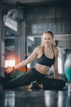 Young attractive woman fitness doing exercises workout with ball in gym. Woman stretching the muscles and relaxing after exercise at fitness gym club.