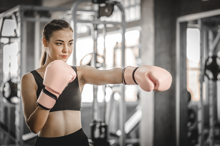 Fit beautiful woman boxer hitting a huge punching bag exercise class in a gym. Boxer woman making direct hit dynamic movement. Healthy, sports, lifestyle, Fitness, workout concept. With copy space. Banco de Imagens
